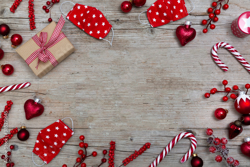 Christmas ornaments and face masks on wooden background, top view