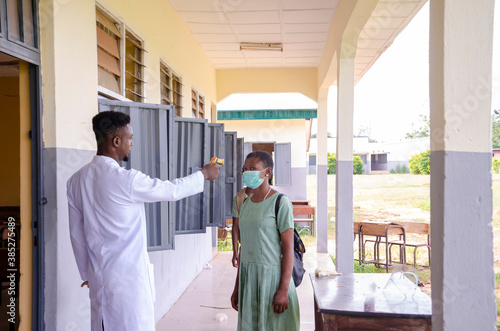 Obraz a young handsome african class teacher holding as thermometer to scan the temperature of his student before entering the classroom - fototapety do salonu