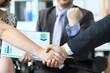 Closeup of man and woman shaking hands in front of smiling man with documents in background. Conducting business deals concept.