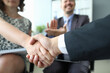 Handshake of man and woman closeup and cheering businessman in background in office. Partner relationship with customers concept.