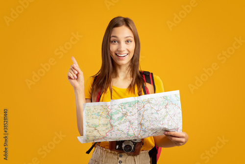 Motiveted young woman tourist holding city map, showing eureka gesture