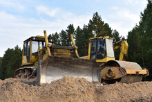 Dozer And Vibro Roller Soil Compactor At Road Construction And Bridge Projects In Forest Area. Heavy Machinery For Road Work. Building A Road Works. Leveling And Compaction Of Soil