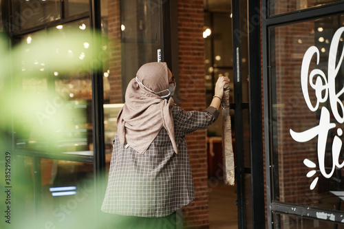 Photo Muslim women are opening the glass doors of the cafe using their elbows in accordance with health protocols, the woman is wearing a medical cloth mask to prevent transmission of the virus