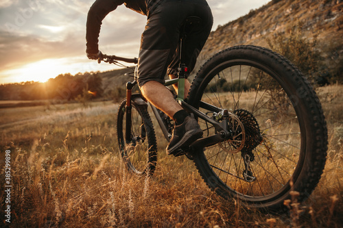 Crop man riding mountain bicycle at sunset Fototapeta