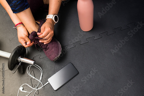 Closeup woman lacing footwear to do exercise at gym with copy space for text. Concept of healthy life and sport. Black rubber floor mat and tiles inside a gym.