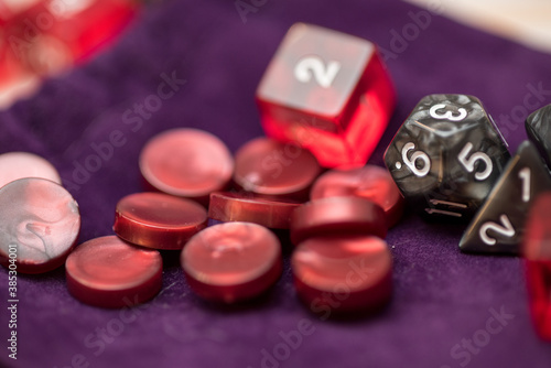 Role playing game dices and tokens lying on a purple bag where they are stored
