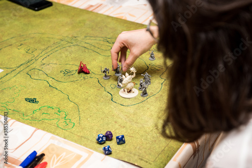 Girl with glasses playing role game dungeons and dragons, miniatures and dices on the green field.