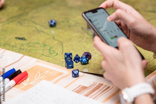 Girl using the smartphone during a role-playing game of dungeons and dragons. Dices on the green battlefield