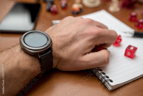 Man wearing a smartwatch ready to play role game like dungeons and dragons with the dices, smartphone and dices.
