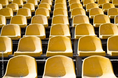 Fototapeta empty yellow seats on outdoor sport stadium arena for football fans, big game