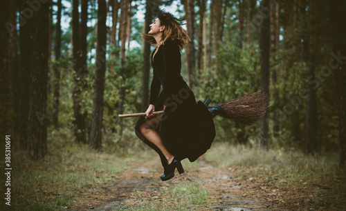 Fotografía Young beautiful and mysterious Witch woman Flying on the Broom in woods