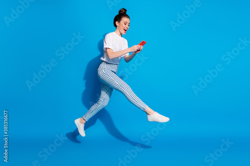 Obraz Full length body size view of nice attractive cheerful carefree girl jumping using technology virtual connection wi-fi having fun isolated on bright vivid shine vibrant blue color background - fototapety do salonu