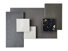 Top View Of Interior Material Board Containing White Grained Synthesis Stone, Black Terrazzo, Grey And Brown Stone Tiles, Dark Wooden Veneer Samples Isolated On White Background With Clipping Path.