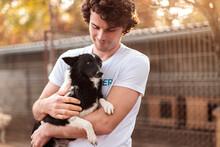Male Volunteer Hugging Dog In ...