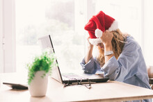 Woman With Santa Claus Hat And Computer With Expression Of Tired Or Overwhelmed