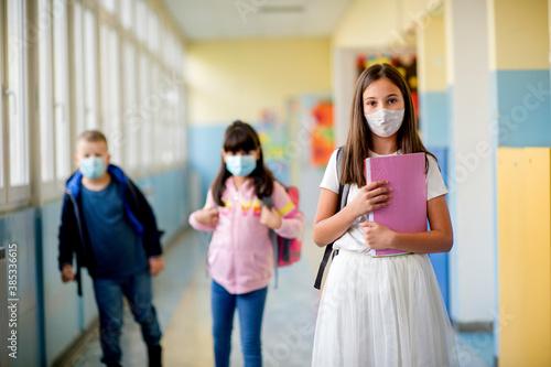 Fotografering Elementary school students walking down the hallway in between classes