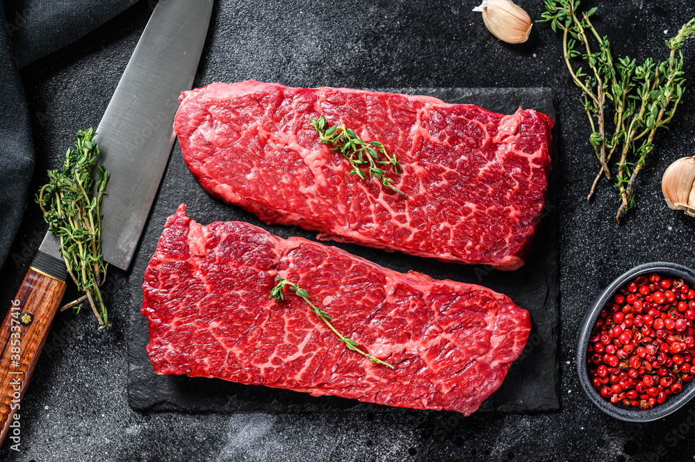 Fototapeta Marble beef Denver steak with herbs. Organic meat. Black background. Top view.