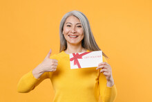 Smiling Cheerful Funny Gray-haired Asian Woman In Casual Clothes Standing Holding In Hand Gift Certificate Showing Thumb Up Looking Camera Isolated On Bright Yellow Colour Background, Studio Portrait.
