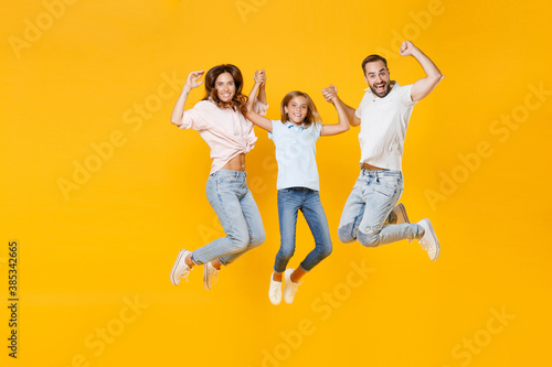 Photo Full length portrait of cheerful young parents mom dad with child kid daughter teen girl in basic t-shirts jumping holding hands isolated on yellow background studio portrait