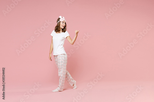 Full length side view portrait of cheerful young woman in white pajamas home wear sleep mask point thumb aside on mock up copy space rest at home isolated on pink background Wallpaper Mural
