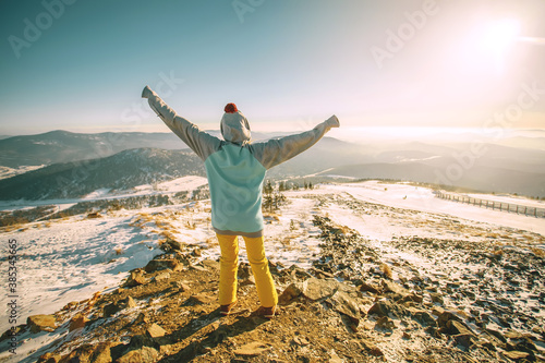 Photo Woman standing on the top, admiring winter mountain landscape