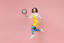 Full Length Side View Portrait Of Excited Young Woman Housewife 20s In Apron Jumping Hold Frying Pan Clenching Fists While Doing Housework Isolated On Pink Background Studio. Housekeeping Concept.