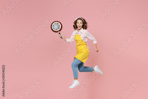 Leinwand Poster Full length side view portrait of excited young woman housewife 20s in apron jumping hold frying pan clenching fists while doing housework isolated on pink background studio