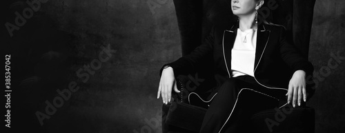 Black and white cropped photo of a woman in a black pantsuit sitting in a high chair in a comfortable position with one leg over the other. Cropped shot with dark gray background.