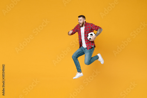 Full length portrait of excited young man football fan in red shirt cheer up support favorite team with soccer ball jumping like running isolated on yellow background. People sport leisure concept.