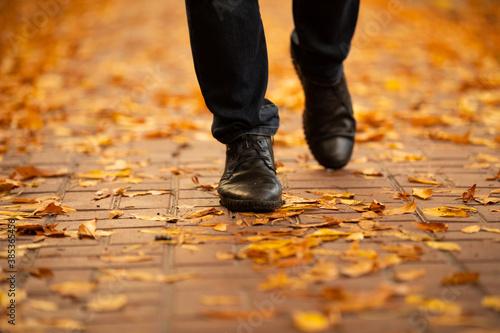 Fotografiet Men boots walking on the sidewalk strewn with autumn leaves