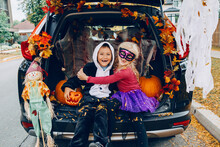 Trick Or Trunk. Children Celebrating Halloween In Trunk Of Car. Boy And Girl With Red Pumpkins Celebrating Traditional October Holiday Outdoors. Social Distance And Safe Alternative Celebration.