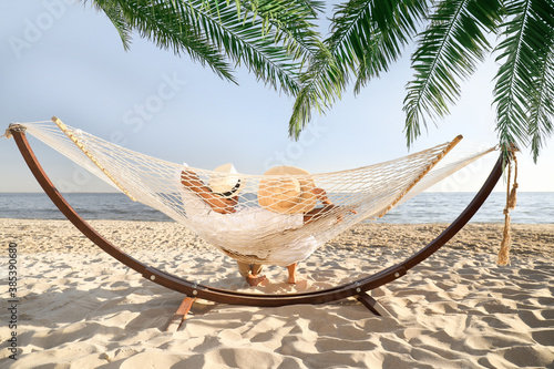 Obraz Couple relaxing in hammock under green palm leaves on beach - fototapety do salonu