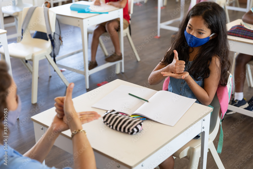 Fototapeta Female teacher and girl wearing face masks talking to each other through sign language in class