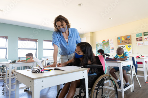 Disable girl wearing face mask writing while sitting on wheelchair in class