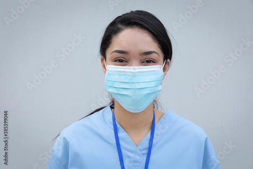 Portrait of female health worker wearing face mask against grey background