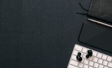 Top View Of Black Screen Smartphone With White Keyboard, Earphone And Notebook On Black Leather Background