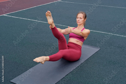 Woman athlete practices yoga exercises, stretches, fitness, lotus position, warrior pose Fototapeta