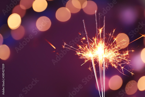Photo Beautiful Christmas sparklers on dark background with blurred lights