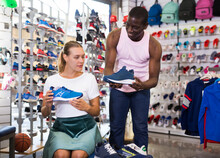 ..Female Customer Trying Sports Shoes In Sporting Goods Shop.