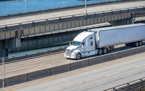 Obraz White bonnet big rig semi truck tractor transporting cargo in refrigerated semi trailer running on the multilevel overpass road intersection along the river - fototapety do salonu