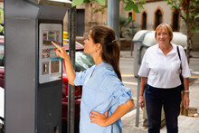 Young Pleasant Serious Positive Woman Paying For Parking In Modern Parking Meter On City Street