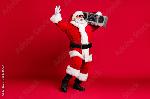Obraz Full length photo of pensioner old man white beard raise hand hold retro radio carefree wear x-mas santa costume gloves coat belt sunglass headwear black boots isolated red color background - fototapety do salonu