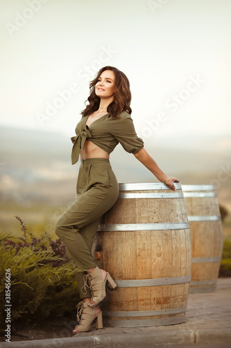 Portrait of beautiful woman smiling with curly hair in hat enjoying at park  by wooden barrel. Autumn Sunset photo.