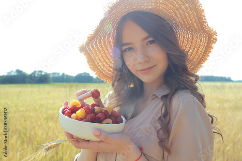 Obraz girl raspberries eating a picnic field sun / adult young model eating raspberries in a sunny summer field, enjoying happiness romance - fototapety do salonu