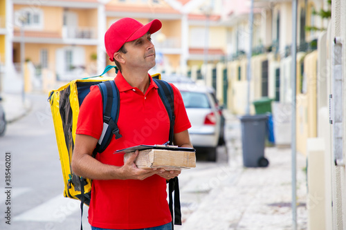 Tela Positive deliveryman holding parcel with clipboard and waiting for recipient outdoors