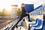 Fototapeta Fototapety na drzwi - Fitness woman in black sportswear training on the stairs in stadium tribune. Street functional training, selective focus.