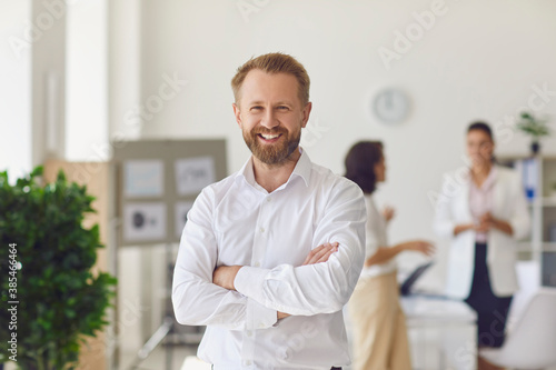 Fotografija Happy successful businessman or company employee standing in office looking at c