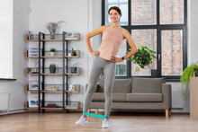 Sport, Fitness, Lifestyle And People Concept - Happy Woman Exercising With Resistance Band At Home