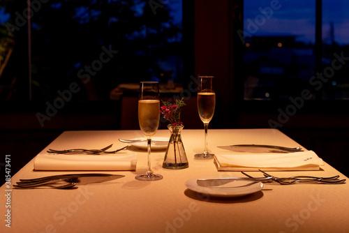 Foto 夜の優雅なフレンチレストランでのディナータイム シャンパングラスとテーブルセッティング