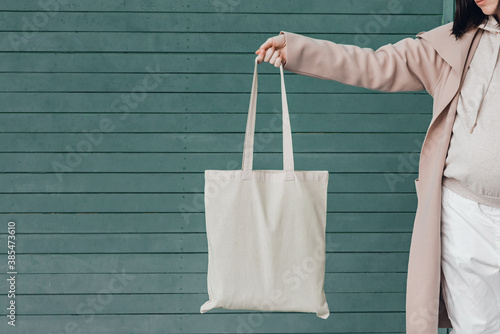 Woman in coat with white cotton bag in her hands Fotobehang